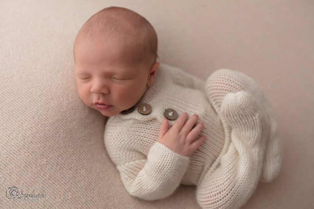 newborn baby boy in cream footie pajamas