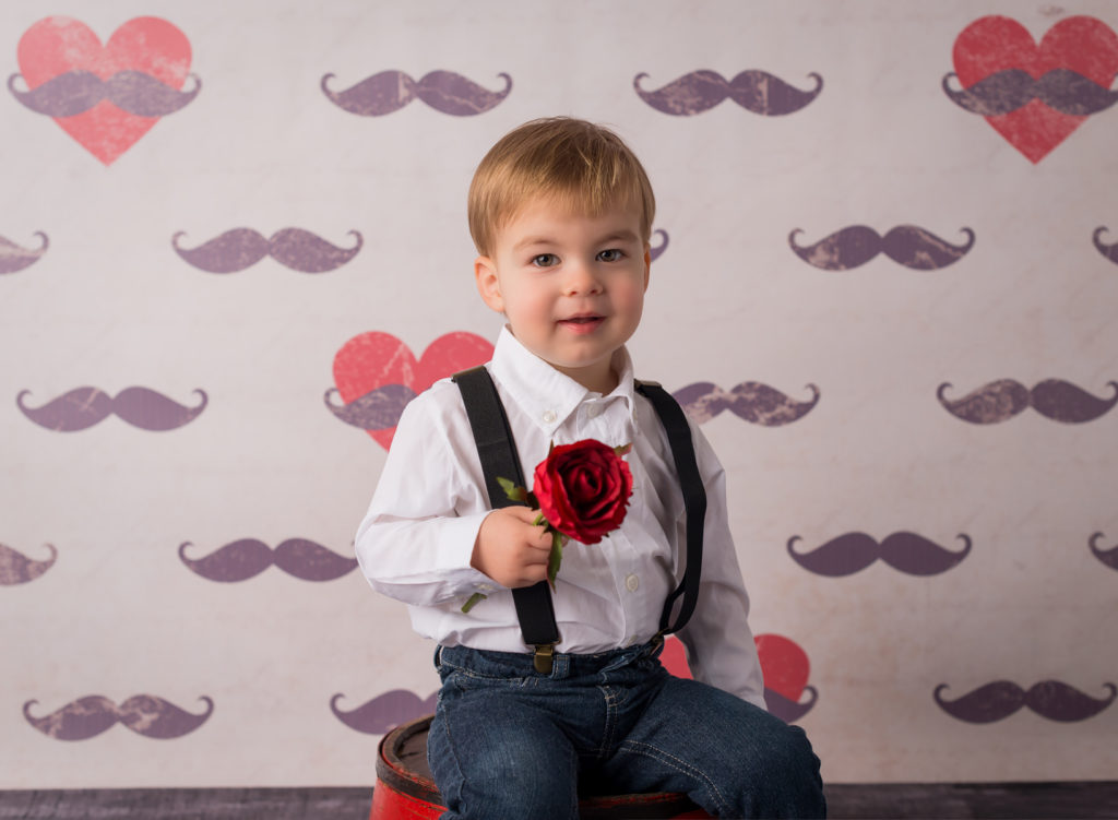 boy photo session with mustache backdrop