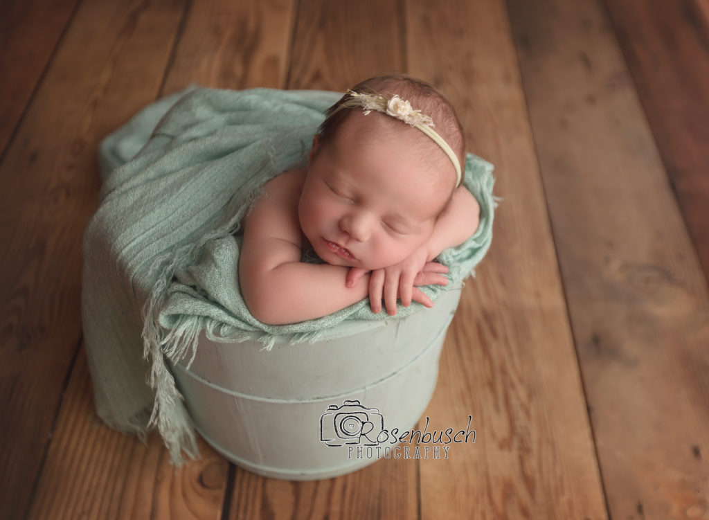 newborn girl posed in bucket