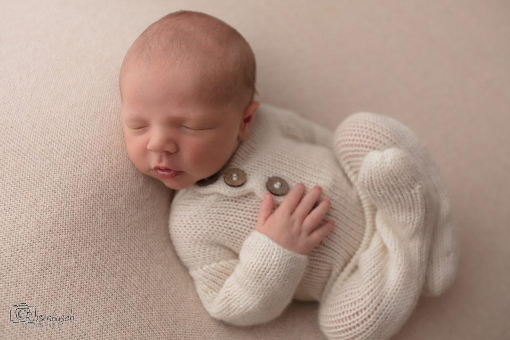 newborn baby boy in cream footie pajamas